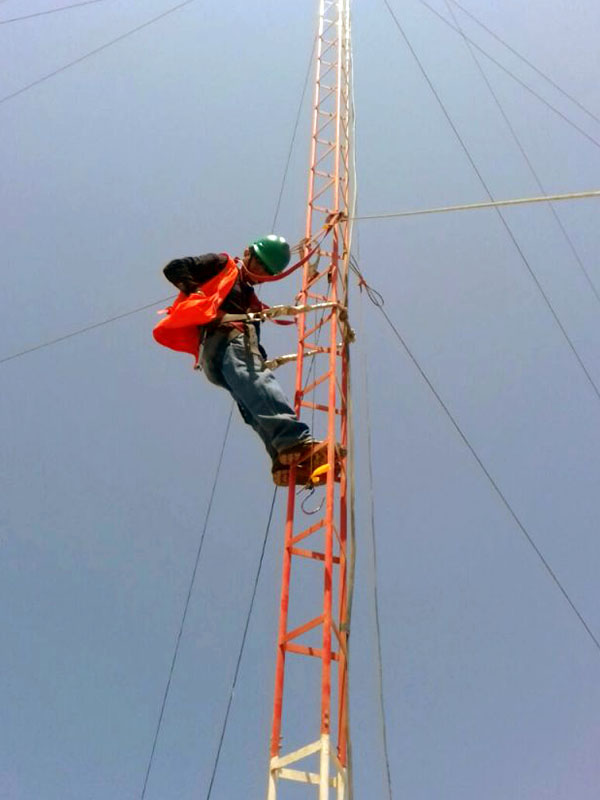 Operario de mantenimiento de una antena trabajando a gran altura.